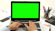 Man hand on laptop keyboard with green screen monitor video