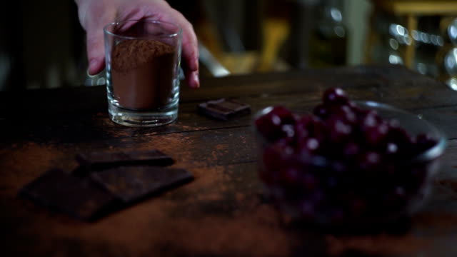 Man hand take glass cup with cocoa powder. Ingredients for baking cake video