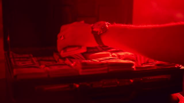 Man hand taking money from case with red backlight. Suitcase full of money video