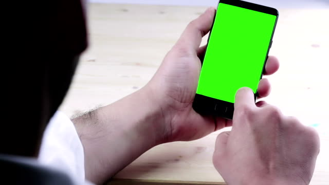 man hand using a smart phone with chroma key on wood table behind view, green screen video