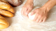 Man hands kneading dough in flour on table. video