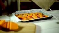Man hands taking pumpkin slices on baking sheet. Recipe baked pumpkin video