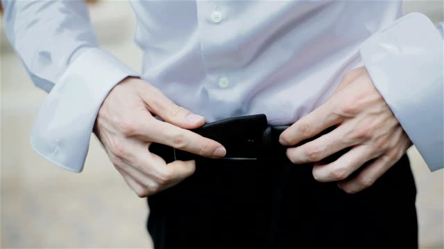 Man hands tighten trendy leather belt for his black trousers on his waist going to work official clothes look. Close-up video