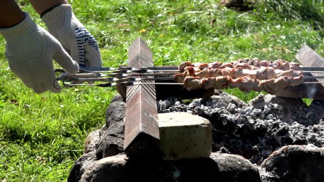 Man hands turn bake skewer with pork meat shashlik on hot ember in stone fireplace. video