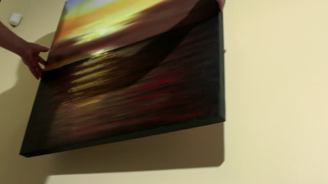 Man hanging seascape sunset oil painting on the wall video