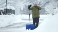 HD: Man Having A Call While Shoveling Snow video