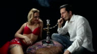 Man having a smoke of water pipe with belly dancer video