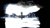 Man having bath in a cave video