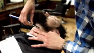 Man having shave at barber shop close up. Professional barber using straight razor with sharp blade and cream gel to cut hair bristles of whiskers at customer face. Happy smiling satisfied barbershop client video