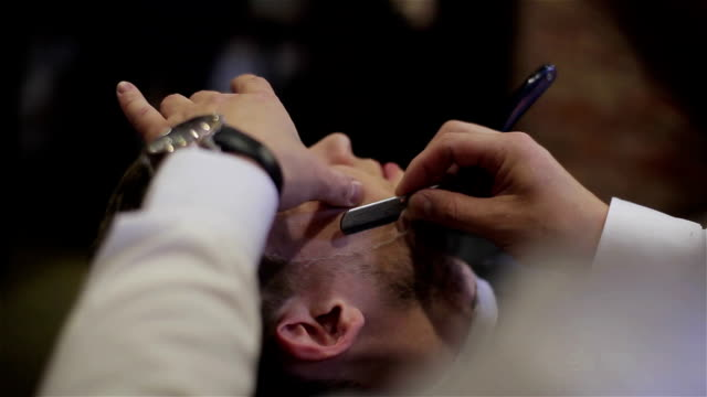 Man having shave at barber shop close up. Professional barber using razor with sharp blade and cream gel to cut hair bristles of whiskers at customer face. Happy smiling satisfied barbershop client video