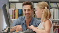 DS Man helping girl learn to use computer in library video