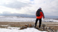 Man hiker walking through the snowy mountain plateau video