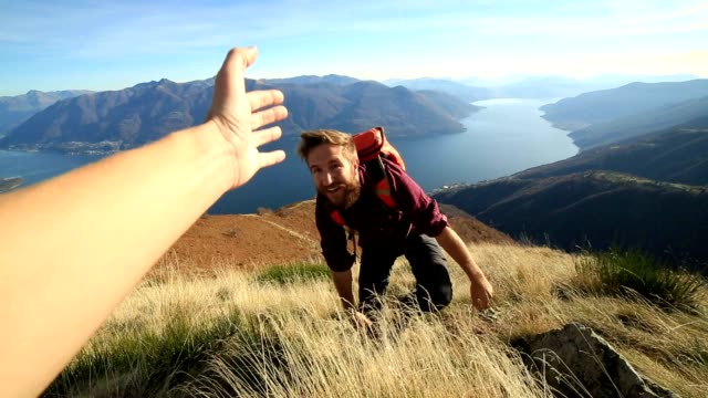 Man hiking on difficult terrain, hand reach out to assist video