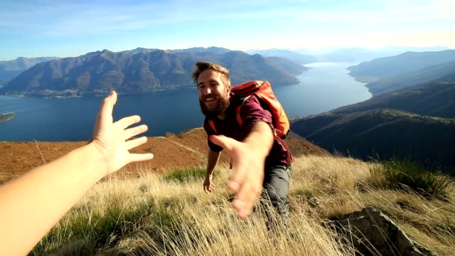 Man hiking uphill, hand reach out to help video
