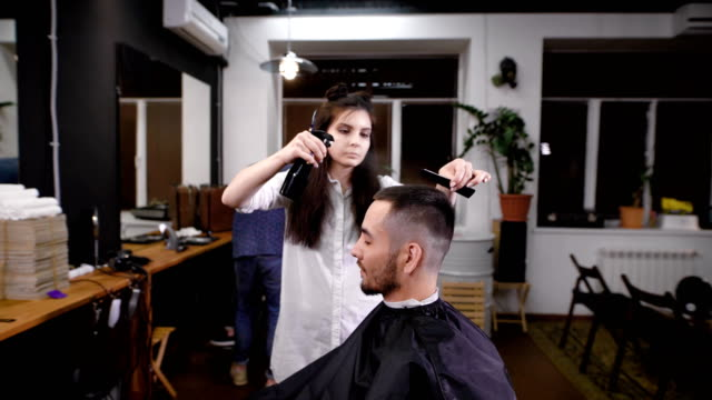 Man hipster visiting barber shop. Woman barber making stylish haircut. View of interior of barber shop video
