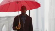 A man holding an umbrella walks towards the camera away the Brooklyn Bridge in slow motion video