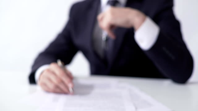 Man holding out key from house or apartment to buyer, signing mortgage agreement video