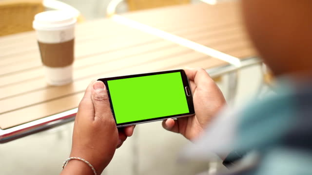 Man Holding Phone With Green Screen Outside at Cafe HD video