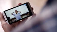 Man Holding Smartphone And Watching Video Of Spinning Girl video