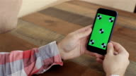 Man Holding Smartphone With Green Touch Screen, Chroma Key For Custom Content.close up video