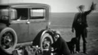 1934: Man holding up hunted dead bird beside model A car. video