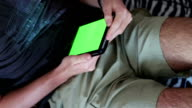 man holds a blank tablet PC with a green screen on sofa video