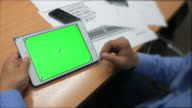 A man holds a blank tablet PC with a green screen video