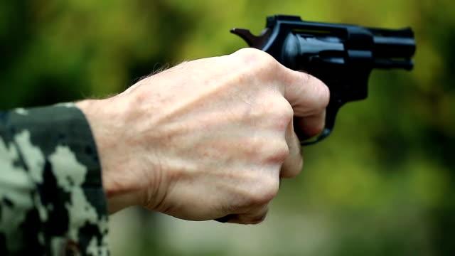 Man holds in hands black revolver video