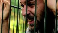 Man imprisoned in a cage gets angry and despairs video