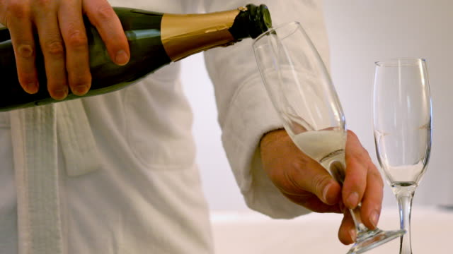 Man in a Bathrobe Pouring Champagne video