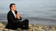 a man in a black suit and tie relaxes on the beach. video