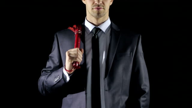 man in a business suit holding a whip for sex games. red skin. love toys video