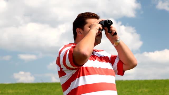 Man in a field look into binoculars video