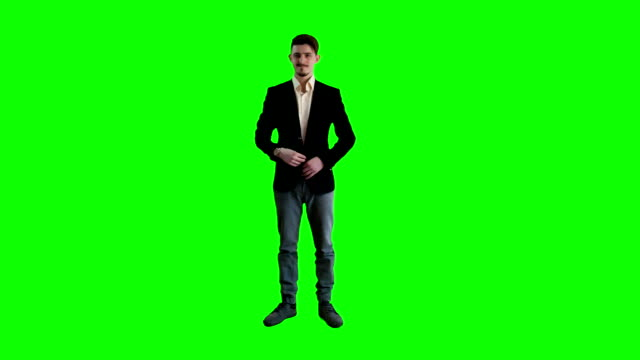 A man in a jacket standing at background of a green screen video