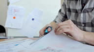 A man in a plaid shirt, a pair of scissors cuts tracing paper which shows plan video