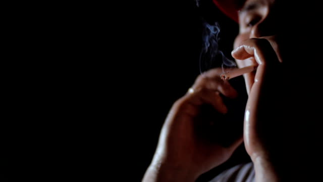 A man in a red baseball cap smokes a cigarette. video