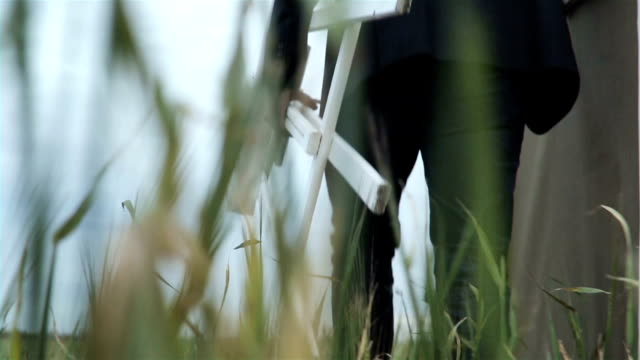 Man In A Suit With His Easel In The Field video