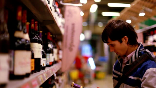 Man in a supermarket choosing a wine. 1920x1080 video