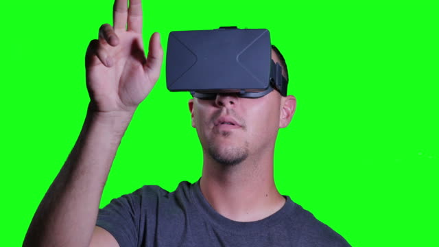 A man in a virtual reality mask looks around and manipulates his surroundings. video