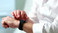 A man in a white shirt uses a smart watch. Close-up. video
