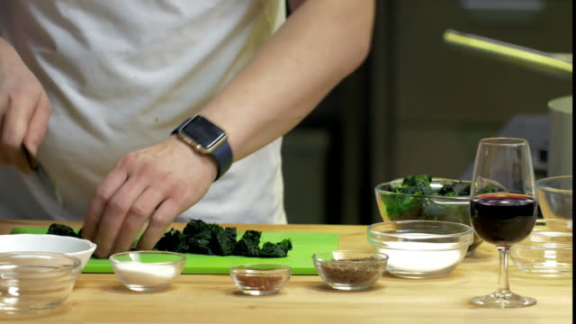 Man in a white T-shirt slice green leek on a cutting board on kitchen video
