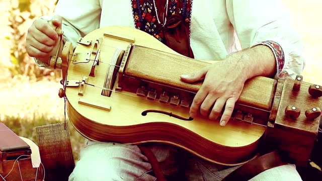 man in ancient clothes playing on the hurdy-gurdy video