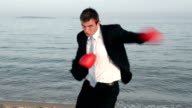 Man in black suit fights at the beach video