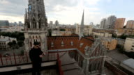 Man in black talking on the phone on roof of building near Catholic cathedral fa video