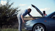 Man in blue jeans having automobile problems video