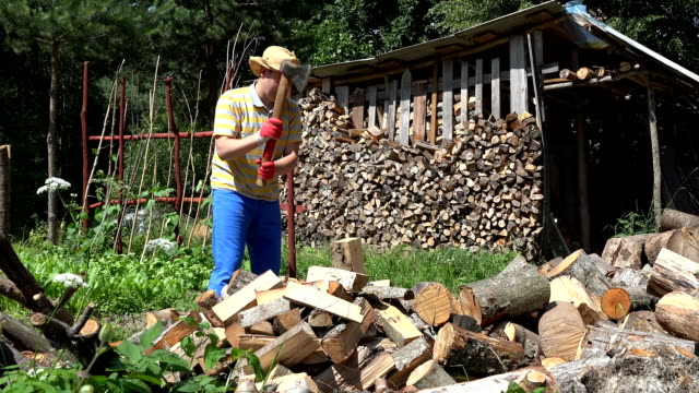 Man in blue pants and straw hat chopping wood in his yard, in village. video
