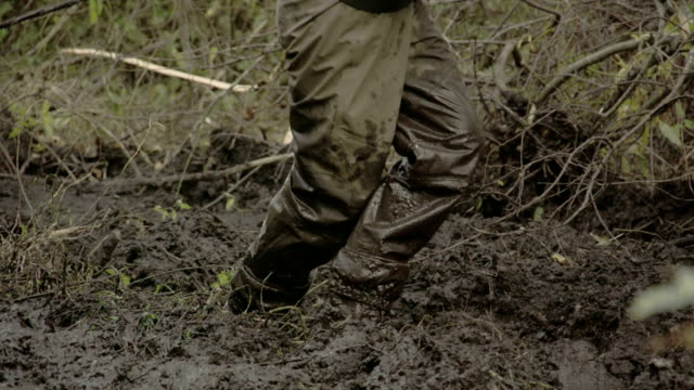 A man in boots walking onto the thick mud video