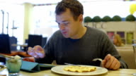 Man in cafe having dinner and using tablet PC video