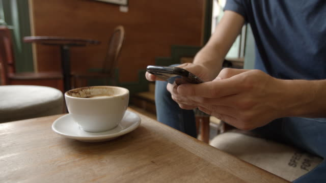 Man in cafe using phone and drinking coffee, close up detail video