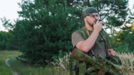 Man in camouflage with guns. Speaking on the radio video